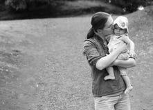 母亲亲吻她的婴孩 免版税库存图片