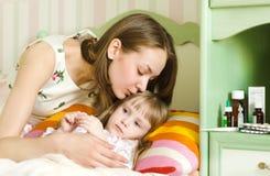 母亲亲吻病的孩子 免版税库存图片
