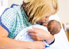 母亲亲吻的新出生的Babygirl在医院 免版税库存照片
