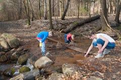 母亲使用与她的一条小河的孩子在早期的春天 免版税库存照片