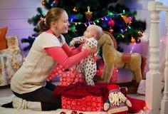 母亲使婴孩脱离在圣诞树和光的背景的礼物盒 免版税图库摄影
