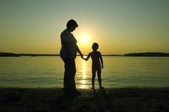 母亲儿子夏天日落 免版税库存照片