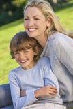母亲儿子妇女坐外面在阳光下的男孩孩子 免版税库存照片