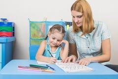 年轻母亲准备一个五年女孩到学校 库存图片
