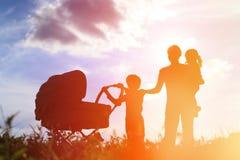 母亲剪影有三个孩子的走在日落的,愉快的家庭 免版税库存图片