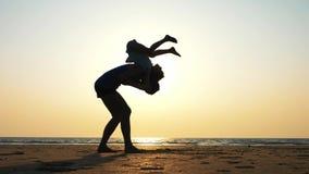 母亲剪影有女儿做的体操在海滩在日落 股票录像