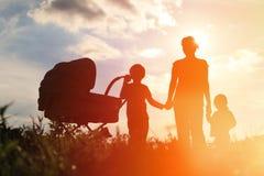 母亲剪影有走在日落的三个孩子的 库存图片