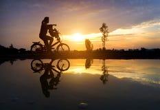 母亲反射剪影有她的小孩的自行车agai的 免版税库存照片