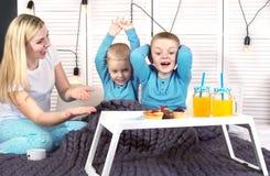 母亲叫醒她心爱的儿子 早餐在孩子的床,惊奇上 库存图片