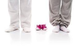 母亲和一双父亲和小小孩子的鞋子的腿 免版税库存图片