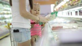 母亲和一点女儿选择冻菜在超级市场 股票录像