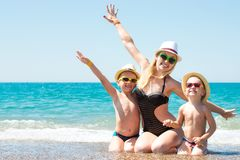 母亲和两个儿子帽子的坐海滩 夏天家庭度假 库存图片