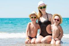 母亲和两个儿子帽子的坐海滩 夏天家庭度假 库存照片