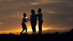 母亲和两个儿子的愉快的家庭父亲剪影使用户外在领域的在日落 股票视频