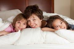 母亲和两个女儿在床上 免版税库存照片