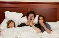 母亲和两个女儿在打呵欠的床上 免版税库存照片