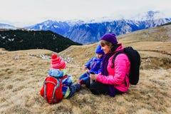 母亲和两个孩子在冬天山旅行 免版税库存照片