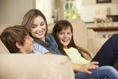 母亲和两个孩子在家坐一起看电视的沙发 免版税图库摄影