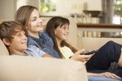 母亲和两个孩子在家坐一起看电视的沙发 库存照片