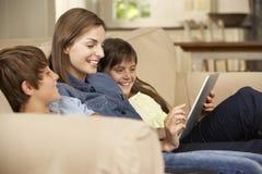母亲和两个孩子在家坐沙发使用片剂计算机 免版税库存图片