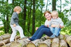 年轻母亲和两个小孩获得乐趣在夏天森林 免版税库存照片