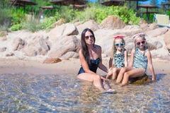 年轻母亲和两她的在异乎寻常的海滩的孩子 免版税库存图片