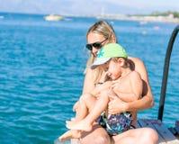 年轻母亲和使用在天计时的海滩的男婴儿子 库存照片