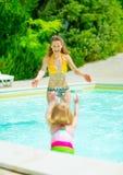 母亲和使用在游泳池的女婴 免版税库存图片