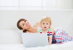 母亲和使用膝上型计算机的惊奇的婴孩 免版税库存照片