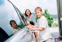 母亲和儿子一起洗涤一辆汽车 库存图片