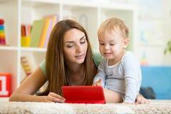 母亲和儿子与片剂个人计算机的儿童游戏 图库摄影