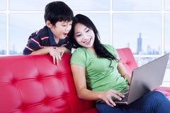 母亲和儿子与膝上型计算机的质量时间在公寓 免版税库存图片