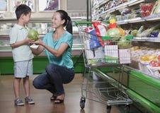母亲和儿子买的西瓜在超级市场,北京 免版税库存照片