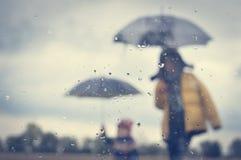 母亲和儿子伞剪影在湿窗口里 免版税库存图片