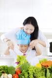 母亲和儿子做午餐的沙拉 免版税库存照片