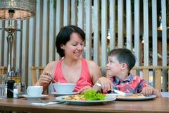 母亲和儿子吃午餐一起在购物中心 库存图片