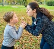 母亲和儿子吹的蒲公英 免版税库存照片