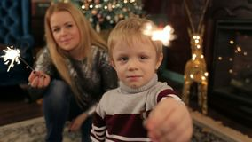 母亲和儿子和闪烁发光物在圣诞树 股票录像