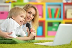 母亲和儿子唱歌卡拉OK演唱 图库摄影