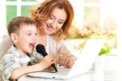 母亲和儿子唱歌卡拉OK演唱 免版税库存照片