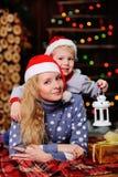 母亲和儿子圣诞老人红色盖帽的背景圣诞灯的 免版税图库摄影