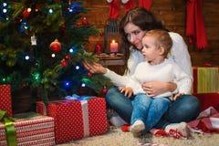 母亲和儿子在一个装饰的房子里庆祝圣诞节 图库摄影