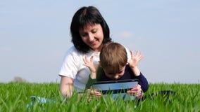 母亲和儿子在公园放松坐绿草 家庭使用一种片剂使用,电影或者做  影视素材