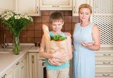 母亲和儿子在有充分纸购物袋的厨房里ve 免版税库存图片