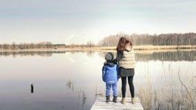 母亲和儿子在码头站立在美丽的池塘 影视素材