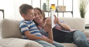母亲和儿子在笔记薄的文字购物清单 股票录像