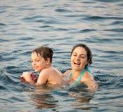 母亲和儿子在水中 免版税库存照片