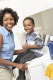母亲和儿子在洗衣房 库存图片