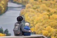 母亲和儿子坐一个高地 秋天 下面河和森林 回到视图 免版税库存照片