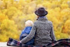 母亲和儿子坐一个高地 秋天 距离的森林 回到视图 免版税库存图片